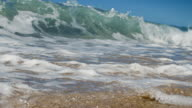 A huge wave breaks over camera on shallow sand beach in the California summer sun. Shot in slow motion on the Red at 200FPS 4K. video