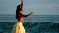 Hula dancer performs by ocean waves, slow motion video