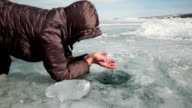 Human feels the water in the ice hole video