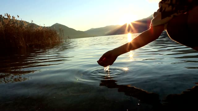 Human hand cupped to catch fresh water from mountain lake video