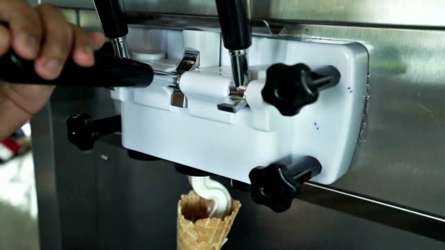 Human hand holding cone with twisted ice cream from machine video