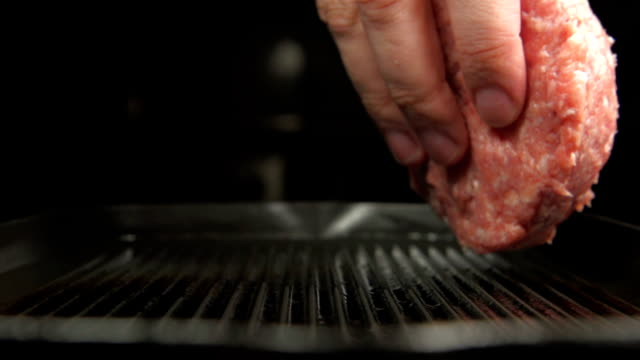SLOW: Human hand puts a fresh beefsteak on a grill video