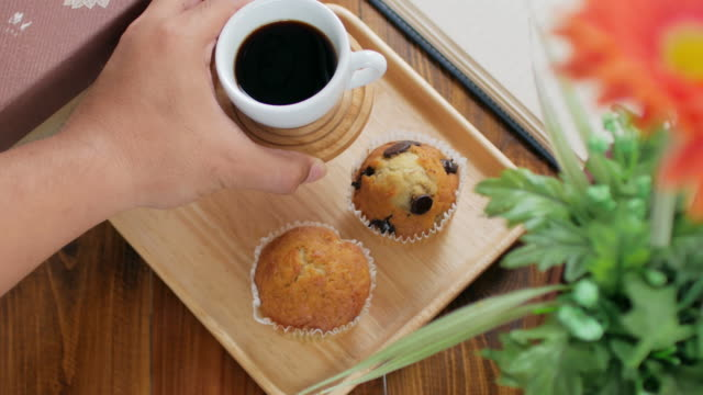 Human hand Setting breakfast set muffin cake and gen serial food with black coffee , dolly shot right to left video