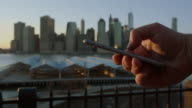 Human hand surfing texting at sunset New York City video