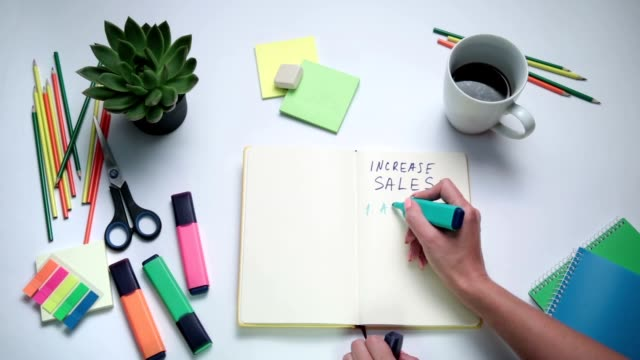 Human hand writing steps to increase sales video
