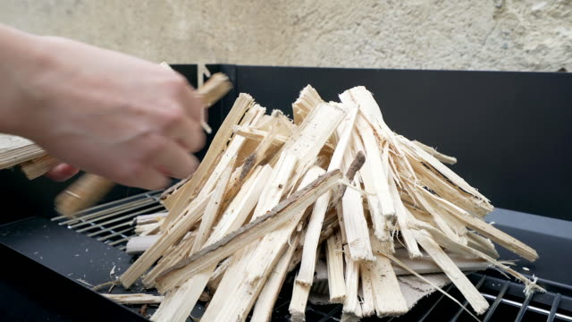 Human hands preparing firewood for a barbeque. video