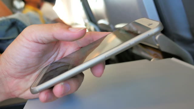 Human hands using smartphone on the airplane,Close-up video