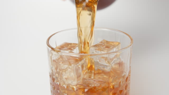 SLOW MOTION: Human pours a whiskey in a glass with an ice cubes from a bottle - close up video