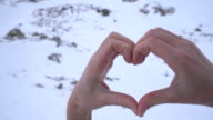 Human's hands making heart shape on snowy mountains landscape video
