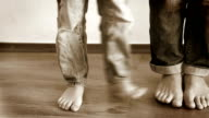 Humorous footage of son's and his mom's feet as they step on each other - wearing denim video