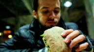 Hungry poor homeless man eating sandwich with vegetables at charity video