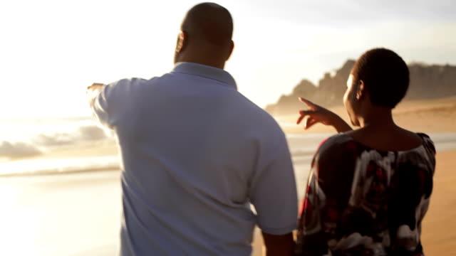 Husband and wife walk on beach video