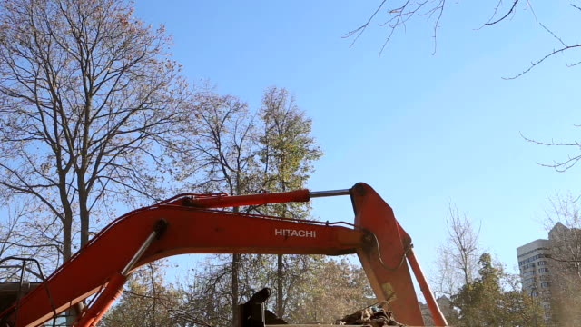 Hydraulic crusher excavator machinery working on demolition old house. Moscow, Russia video