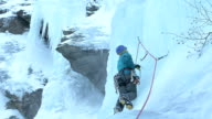 Ice climber on frozen waterfall in winter video