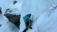 Ice climber placing protection equipment video