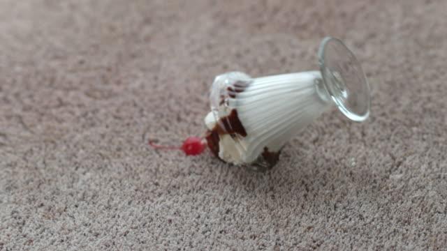 Ice cream sundae spilling on carpet in slow motion video