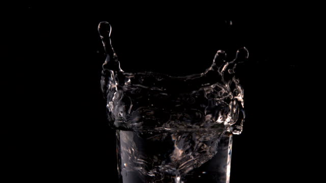 Ice cube falling into glass of water on black background video