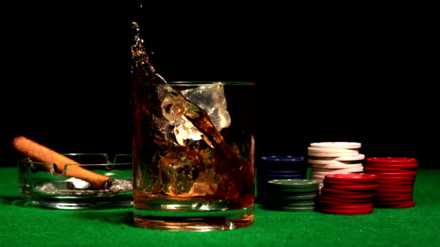 Ice cube falling into glass of whisky on casino table video