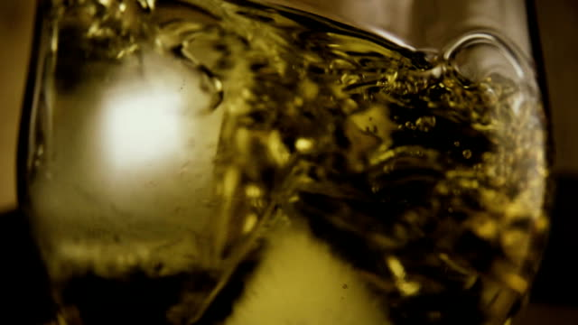 Ice cubes fall into a glass with alcohol. Slow mo video