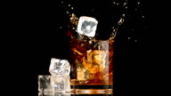 Ice cubes falling into glass of whiskey and ice video