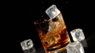 Ice cubes falling into glass of whiskey video