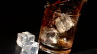 Ice cubes falling into tumbler of whiskey and ice video