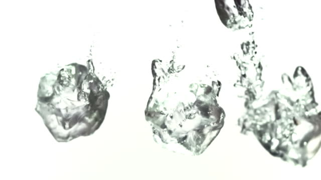 Ice cubes splashing into water in slow-motion video