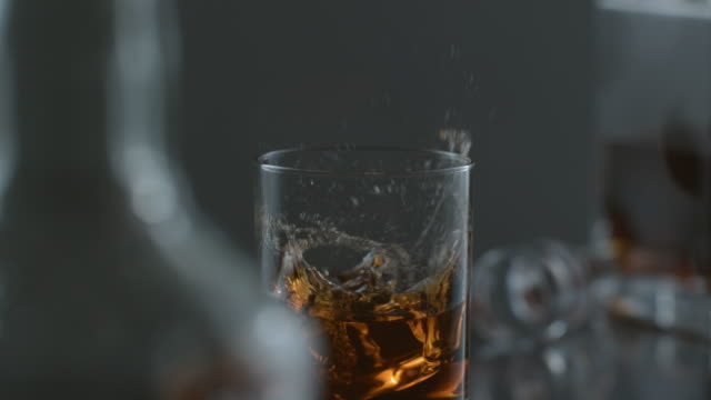 Ice dropped into glass of whisky in slow motion video