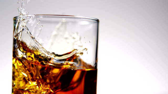 Ice falling into tumbler of whiskey and ice video
