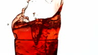 Ice into cranberry juice, slow motion video
