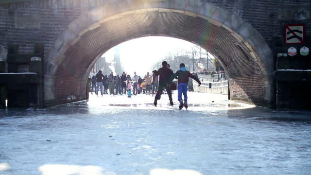 Ice Skating On Frozen Amsterdam Canal under a Bridge video