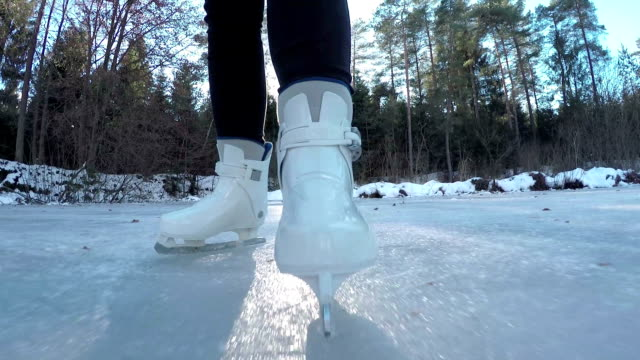 CLOSE UP: Ice skating on frozen pond in sunny forest video