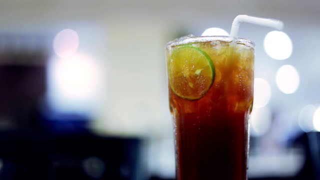 Iced tea with lime slice and blurred restaurant background video