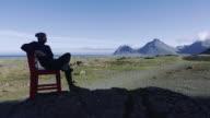 Iceland landmark, big red chair standing among the rocks video