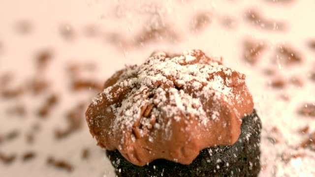 Icing sugar being sieved on chocolate frosted cupcake video