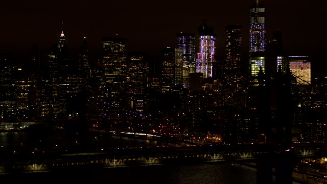 AERIAL: Iconic downtown Manhattan skyline with the two bridges lit up at night video