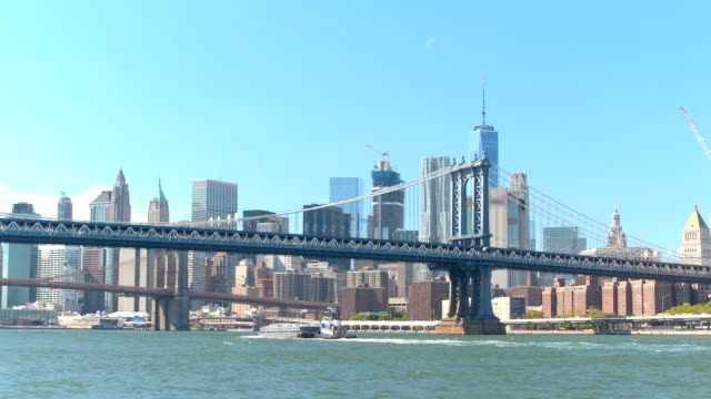LOW ANGLE: Iconic tug traveling under Manhattan bridge towards Brooklyn bridge video