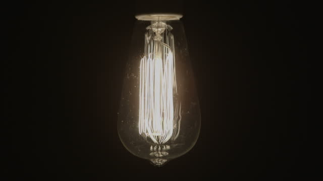 Idea Concept Vintage light bulb turns on with black background video