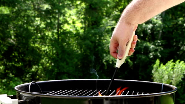 Igniting a charcoal grill in the summer video