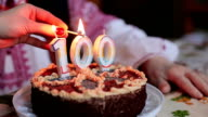 Ignition of candles on the cake. 100 anniversary video