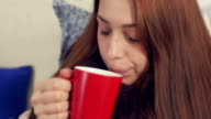 Ill woman drinking hot tea. Suffering from cold video