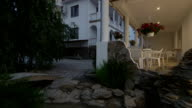Illuminated back garden of two storey house with white balustrade video