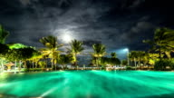 Illuminated night pool against the backdrop of palm trees and the sea. FullHD Timelapse - Bali, Indonesia video