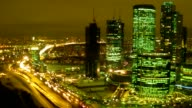 Illumination of night city: skyscrapers, movement on highway. video