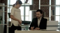 Image of businesswoman  pointing document to businessman   for signature  at the office video