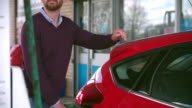 Impatient man refuelling a car at a petrol station video