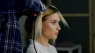 in a beauty salon eccentric stylist makes professional styling for the girls. hairstyle for blonde video