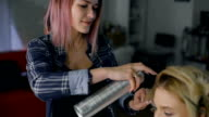 In a beauty salon. The stylist and client, communicate as friends, laughing. Professionalnaf hairstyle video