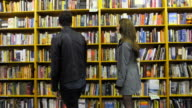 In a bookstore, an attractive couple pause to examine some books video