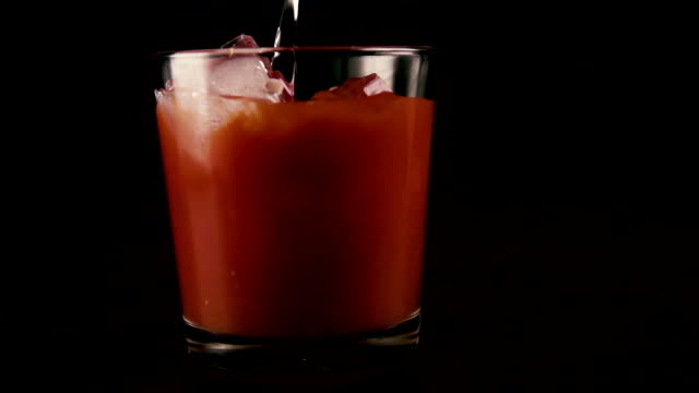 In a glass with ice and juice to pour vodka. Slow motion video